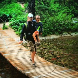 Chris Taylor and LittleMan crossing suspension bridge Glacier National Park