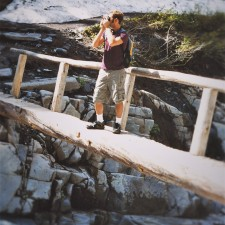 Chris Taylor crossing Log Bridge over Nisqually River in Mt Rainier National Park 2traveldads.com