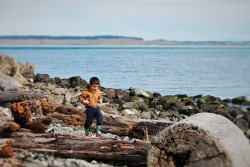LittleMan walking on driftwood at Point Wilson Lighthouse Fort Worden Port Townsend 3