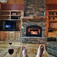 Rob Taylor feet and wine with stone fireplace in John Muir House at Evergreen Lodge at Yosemite National Park 1