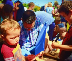 Chris Taylor and Kids building boats at Anacortes Waterfront festival 2traveldads.com