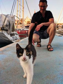 Chris Taylor petting cat in port at Milna Brac Croatia 1