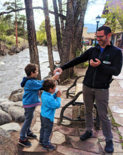 Taylor family walking along Big Thompson River in Downtown Estes Park Colorado 3
