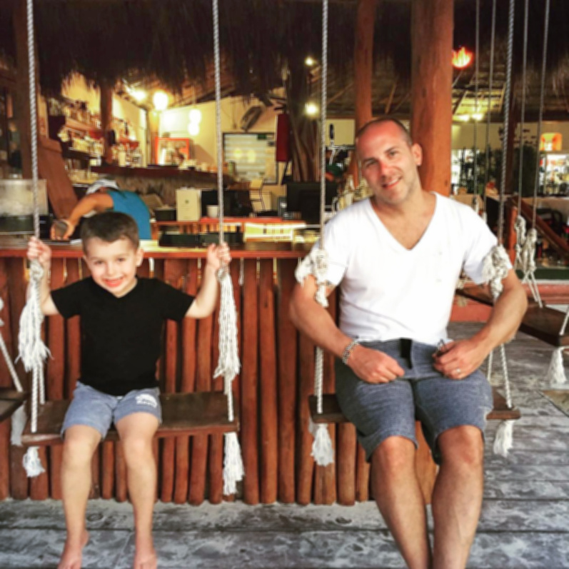 Frank and son FIAB heart on swings in restauarant of Isla Mujeres Quintana Roo Mexico 1