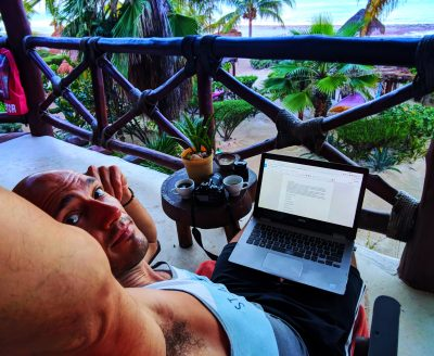 Rob Taylor with Laptop on balcony at sunrise Villas Flamingos Isla Holbox Yucatan 1