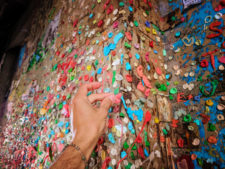Putting gum on Post Alley Gum Wall Downtown Seattle 1