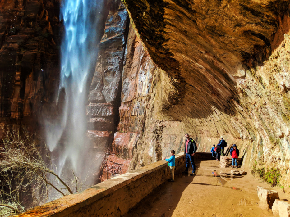 Taylor Family behind waterfall at Weeping Wall trail Zion National Park Utah 3